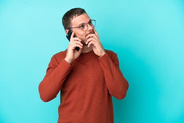 Молодой бразильский мужчина с помощью мобильного телефона изолирован на синем фоне, глядя вверх, улыбаясь