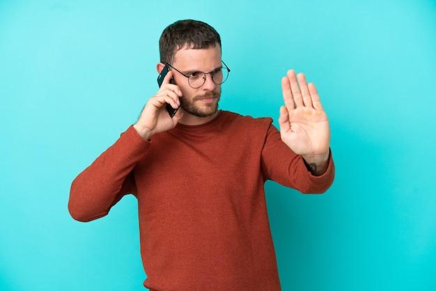 Молодой бразильский мужчина с помощью мобильного телефона изолирован на синем фоне, делая жест стоп и разочарованный