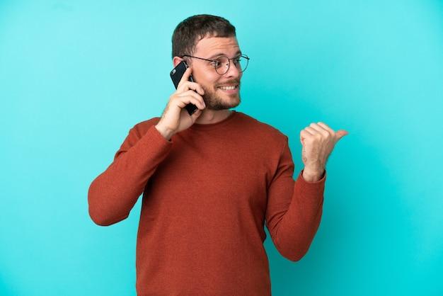 製品を提示する側を指している青い背景で隔離の携帯電話を使用して若いブラジル人男性