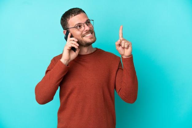 Молодой бразильский мужчина с помощью мобильного телефона изолирован на синем фоне, указывая на отличную идею