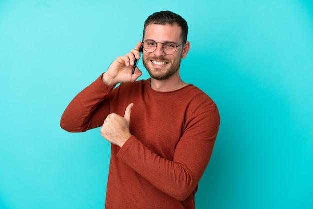 Молодой бразильский мужчина с помощью мобильного телефона изолирован на синем фоне, гордый и самодовольный