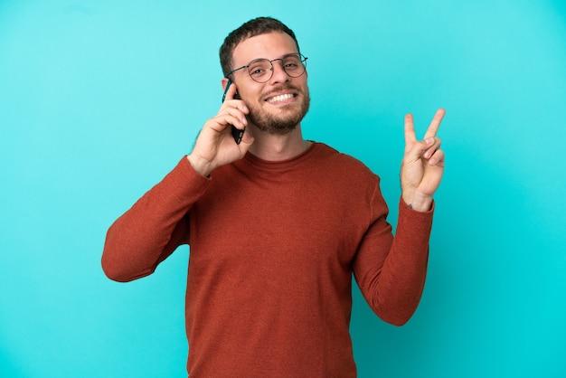 Молодой бразильский мужчина с помощью мобильного телефона изолирован на синем фоне, улыбаясь и показывая знак победы