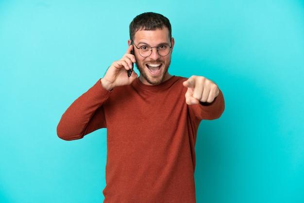 Молодой бразильский мужчина с помощью мобильного телефона, изолированного на синем фоне, удивился и указал вперед