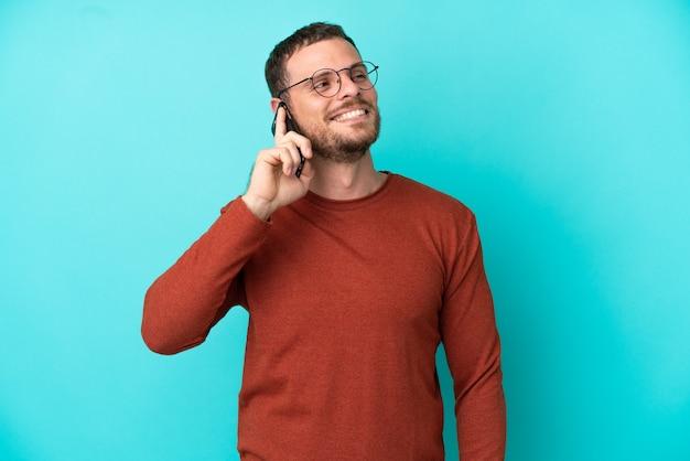 Молодой бразильский мужчина с помощью мобильного телефона изолирован на синем фоне, думая об идее, глядя вверх