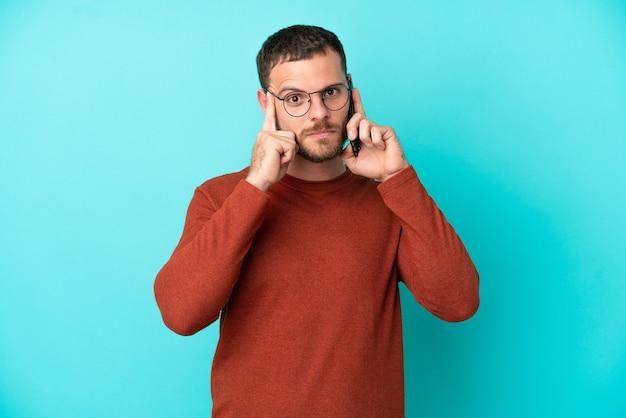파란색 배경에 격리된 휴대 전화를 사용하여 아이디어를 생각하는 젊은 브라질 남자