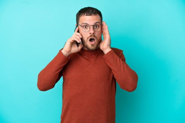 Молодой бразильский мужчина разговаривает по мобильному телефону на синем фоне с удивленным и шокированным выражением лица