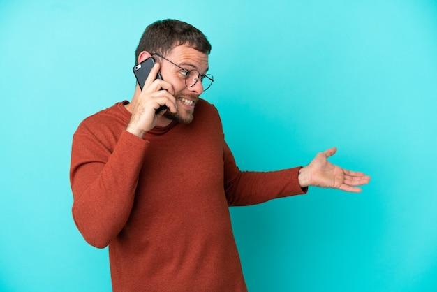 Молодой бразильский мужчина с помощью мобильного телефона изолирован на синем фоне с удивленным выражением лица, глядя в сторону