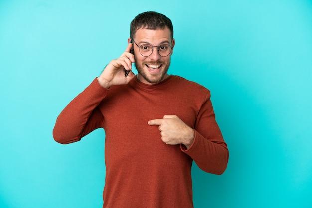 Молодой бразильский мужчина разговаривает по мобильному телефону на синем фоне с удивленным выражением лица