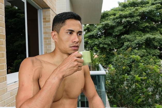 上半身裸の若いブラジル人が、建物のバルコニーでコーヒーを飲んでいる。