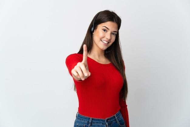 격리 된 벽을 통해 젊은 브라질 텔레마케터 소녀 보여주는 손가락을 들어 올려