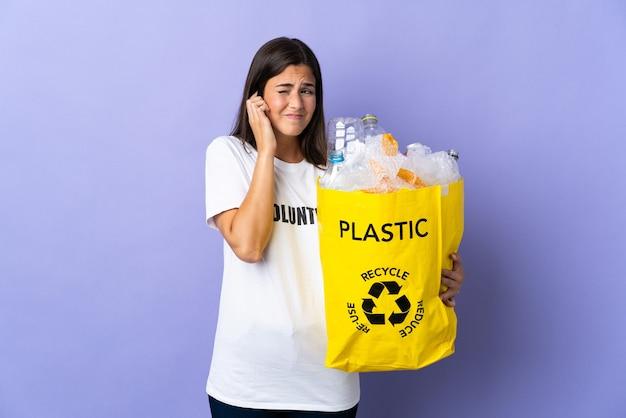 ペットボトルでいっぱいのバッグを持ってリサイクルする若いブラジル人女性は、紫色の欲求不満と円錐形の耳に分離されました