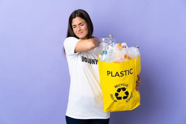 플라스틱 병으로 가득 찬 가방을 들고 젊은 브라질 여자는 노력을 한 데 대한 어깨 통증으로 고통받는 보라색에 고립 된 재활용