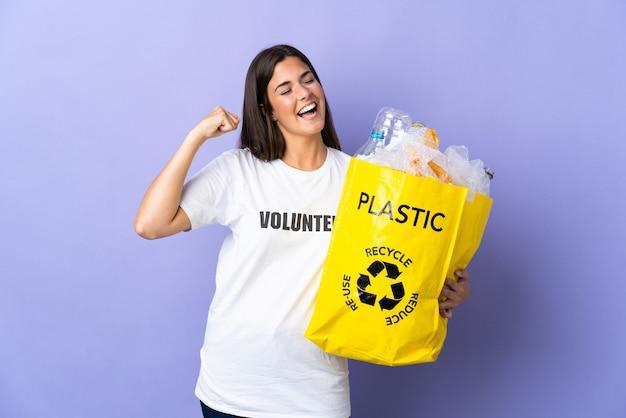 승리를 축하하는 보라색 벽에 고립 된 재활용 플라스틱 병으로 가득 찬 가방을 들고 젊은 브라질 여자