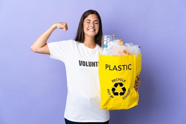 강한 제스처를 하 고 보라색 벽에 고립 된 재활용 플라스틱 병의 전체 가방을 들고 젊은 브라질 여자