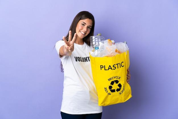 재활용 플라스틱 병의 전체 가방을 들고 젊은 브라질 여자는 행복하고 손가락으로 세 세 보라색 벽에 고립