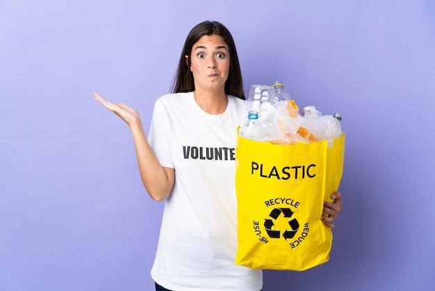 손을 올리는 동안 의심을 갖는 보라색 벽에 고립 재활용 플라스틱 병으로 가득한 가방을 들고 젊은 브라질 여자