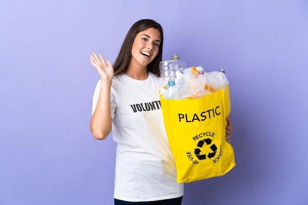 행복 한 표정으로 손으로 경례 보라색 벽에 고립 된 재활용 플라스틱 병의 전체 가방을 들고 젊은 브라질 여자