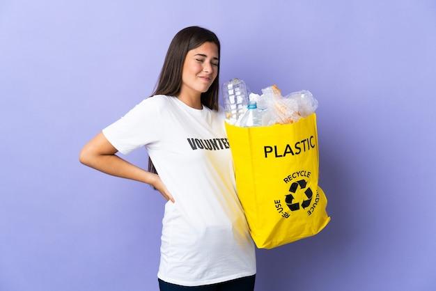 플라스틱 병으로 가득 찬 가방을 들고 젊은 브라질 여자는 노력을 한 데 대한 요통으로 고통받는 보라색 벽에 고립 된 재활용