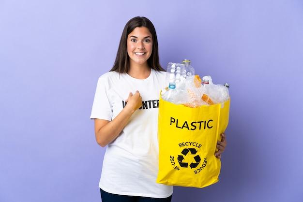 깜짝 표정으로 보라색 벽에 고립 된 재활용 플라스틱 병으로 가득 찬 가방을 들고 젊은 브라질 여자