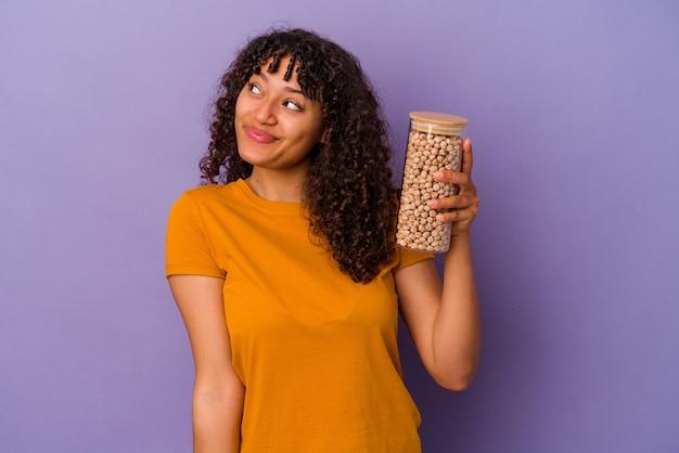 Молодая бразильская женщина держит бутылку нута, изолированную на фиолетовом фоне, мечтает о достижении целей и задач