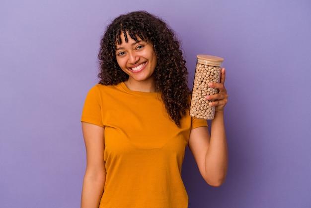 Молодая бразильская женщина держит бутылку нута, изолированную на фиолетовом фоне, счастливой, улыбающейся и веселой.