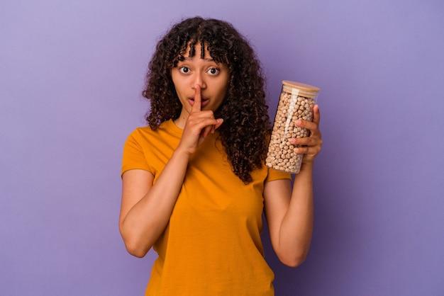Молодая бразильская женщина держит бутылку нута, изолированную на фиолетовом фоне, храня в секрете или прося молчания.