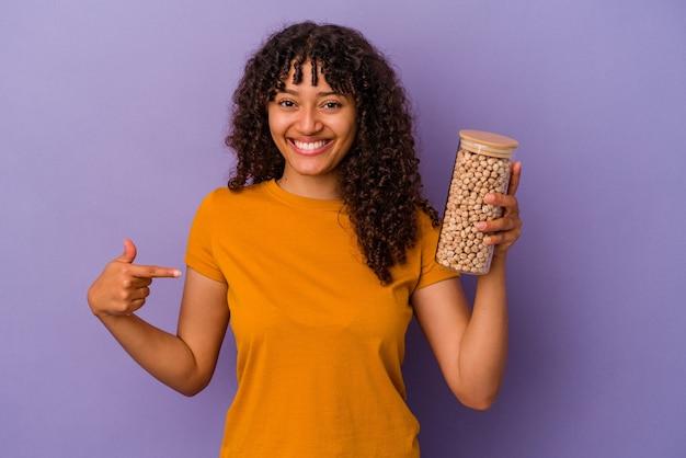 誇りと自信を持って、シャツのコピースペースを手で指している紫色の背景の人に分離されたひよこ豆のボトルを保持している若いブラジル人女性