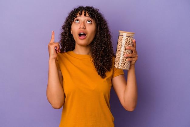 Молодая бразильская женщина держит бутылку нута, изолированную на фиолетовом фоне, указывая вверх дном с открытым ртом.