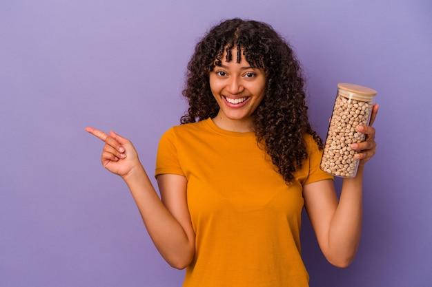 Молодая бразильская женщина держит бутылку нута, изолированную на фиолетовом фоне, улыбаясь и указывая в сторону, показывая что-то на пустом месте.
