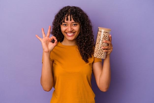 Молодая бразильская женщина, держащая бутылку нута, изолированную на фиолетовой стене, жизнерадостная и уверенная, показывая одобренный жест.