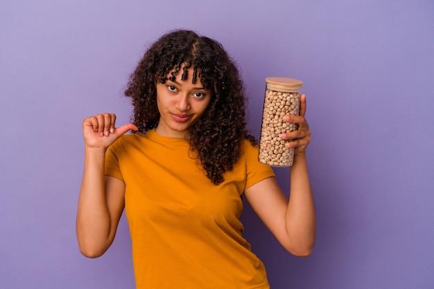 Молодая бразильская женщина, держащая бутылку нута, изолированную на фиолетовой стене, чувствует гордость и уверенность в себе, пример для подражания.