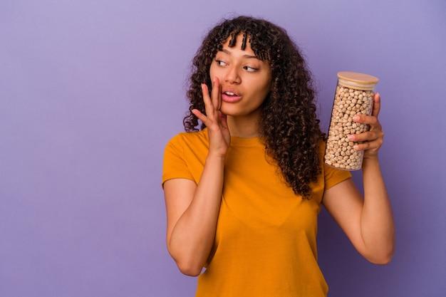 Молодая бразильская женщина, держащая бутылку нута, изолированную на фиолетовой стене, говорит секретные горячие новости о торможении и смотрит в сторону