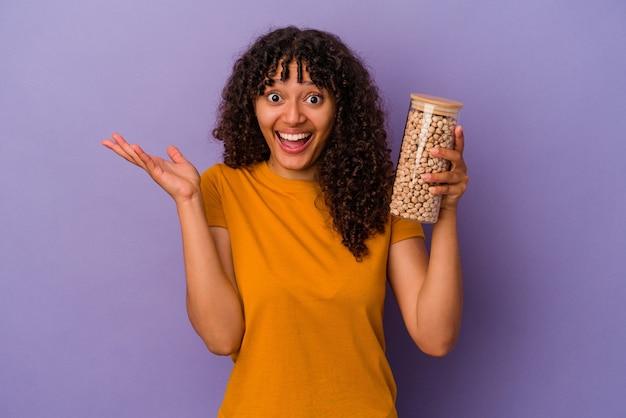 Молодая бразильская женщина держит бутылку нута, изолированную на фиолетовой стене, получая приятный сюрприз, взволнованный и поднимающий руки.