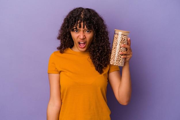 Молодая бразильская женщина, держащая бутылку нута, изолирована на фиолетовой стене, кричала очень сердито и агрессивно.