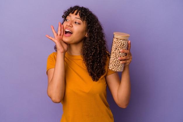 Молодая бразильская женщина, держащая бутылку нута, изолированную на фиолетовой стене, кричит и держит ладонь возле открытого рта.