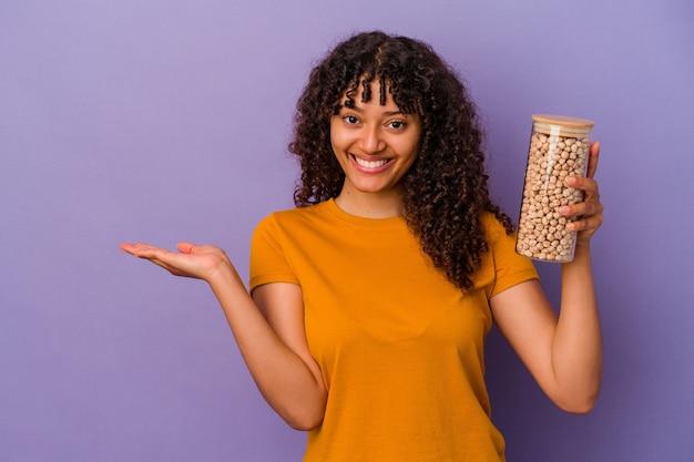 Молодая бразильская женщина, держащая бутылку нута, изолированную на фиолетовой стене, показывает место для копии на ладони и держит другую руку на талии.