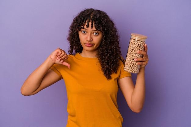 Молодая бразильская женщина держит бутылку нута, изолированную на фиолетовой стене, показывая жест неприязни, пальцы вниз. концепция несогласия.