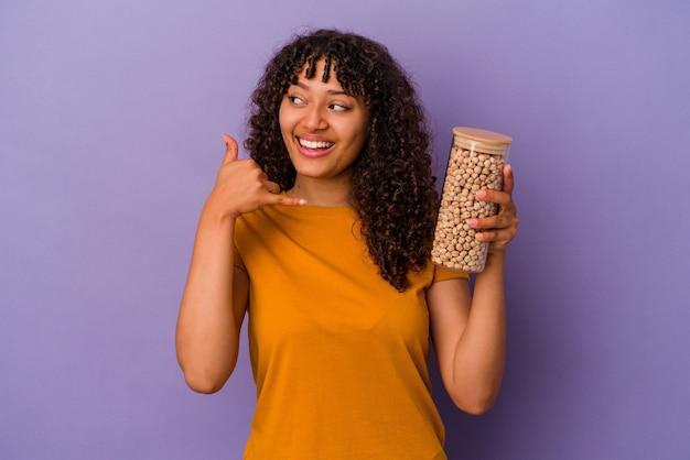 Молодая бразильская женщина держит бутылку нута, изолированную на фиолетовой стене, показывая жест мобильного телефона пальцами.