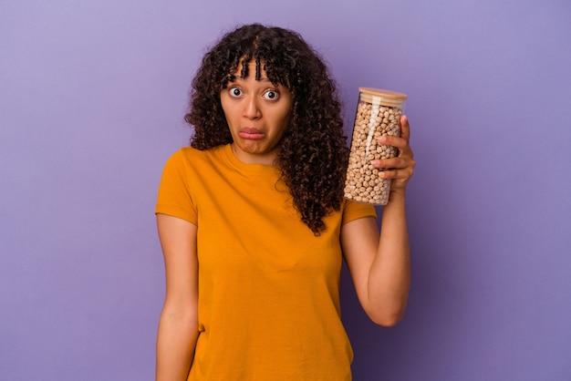 Молодая бразильская женщина, держащая бутылку нута, изолированную на фиолетовой стене, пожимает плечами и смущенно открывает глаза.