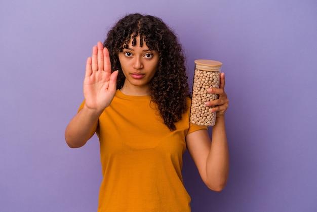 Молодая бразильская женщина держит бутылку нута, изолированную на фиолетовой стене, стоящей с протянутой рукой, показывая знак остановки, предотвращая вас.