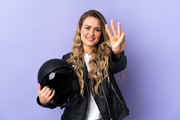 幸せな紫と指で3つを数えるに分離されたオートバイのヘルメットを保持している若いブラジル人女性