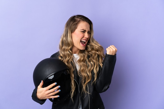 Young brazilian woman holding a motorcycle helmet isolated on purple celebrating a victory