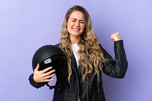 Young brazilian woman holding a motorcycle helmet isolated on purple doing strong gesture