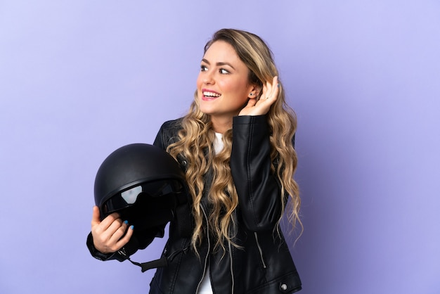 Young brazilian woman holding a motorcycle helmet isolated on purple listening to something by putting hand on the ear