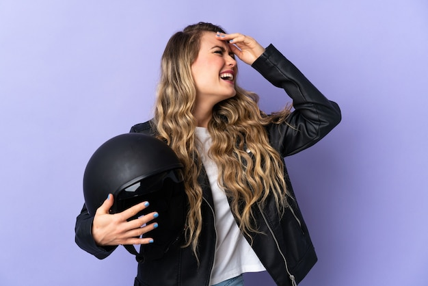 Young brazilian woman holding a motorcycle helmet isolated on purple smiling a lot