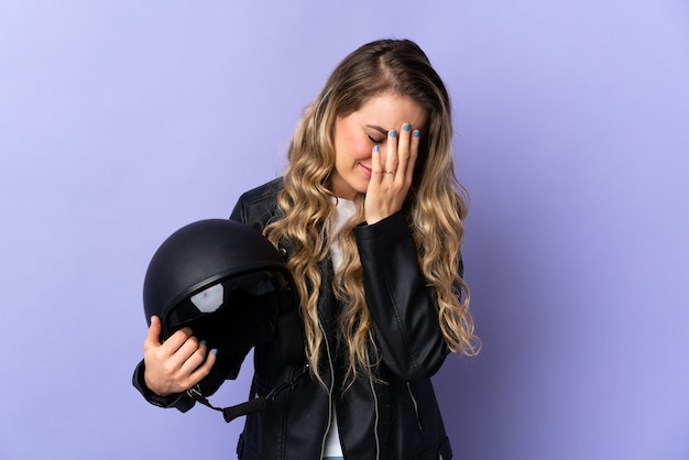Young brazilian woman holding a motorcycle helmet isolated on purple with tired and sick expression