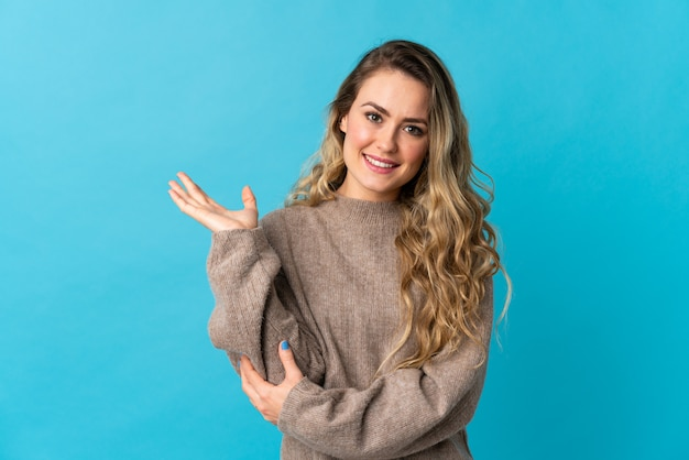 Young brazilian woman isolated on blue extending hands to the side for inviting to come