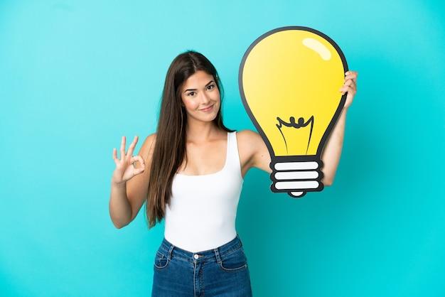 電球のアイコンを保持し、okサインをしている青い背景で隔離の若いブラジル人女性