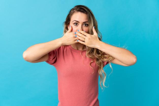 Молодая бразильская женщина изолирована на синем прикрытии рта руками