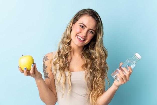 リンゴと水のボトルで青で隔離の若いブラジル人女性